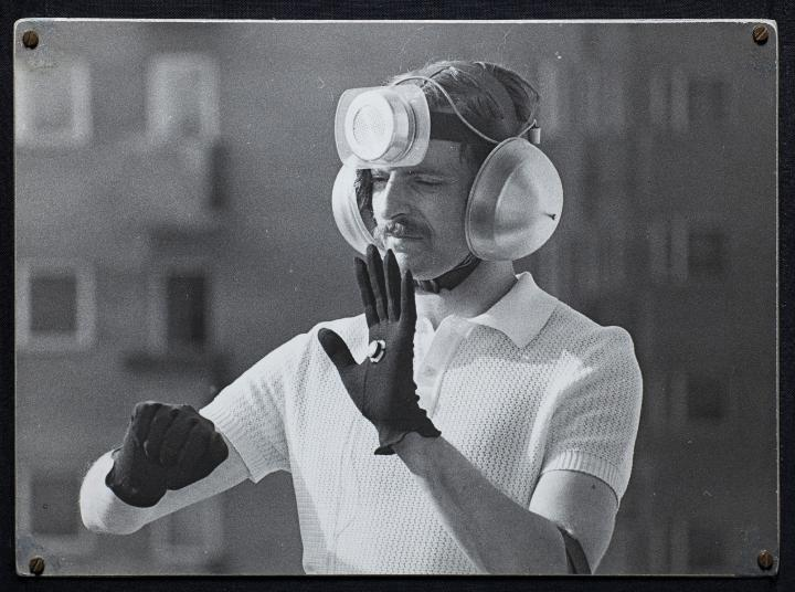 The black and white photo shows a man with a technical installation on his head, his ears covered with sound barriers.