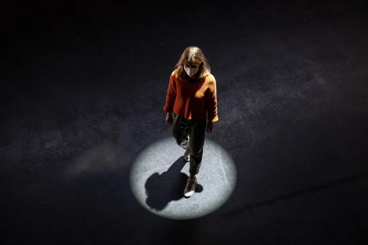 Zu sehen ist eine Frau, die über einen schwarzen Boden läuft und von einem kreisrunden Scheinwerfer anstrahlt wird.