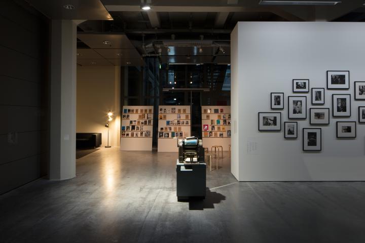 Blick in die Ausstellung »Beat Generation«: Zu sehen sind im Hintergrund einige Bücher, im Zentrum eine alte Druckmaschine und am rechten Rand mehrere Schwarz-Weiß-Fotografien