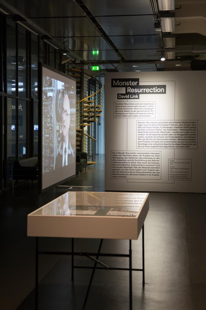 Blick in die Ausstellung »Monster Resurrection«: Eine Projektion, eine Wand mit Beschriftung, eine Vitrine