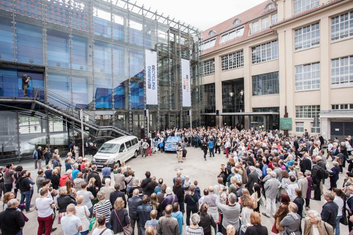 A crowd in front of ZKM entrance gathered around a blue car