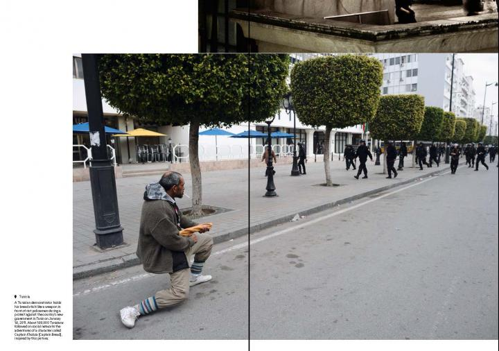Man holding a bread as if it was a gun.