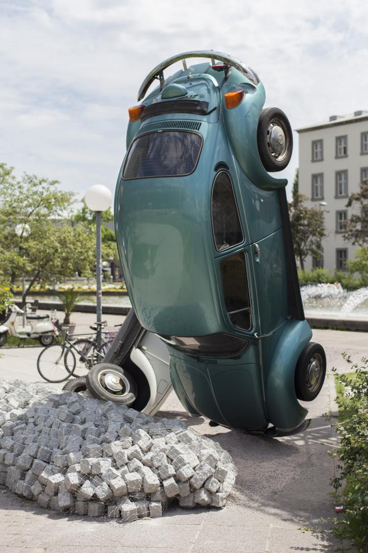 A green VW beetle standing on its head