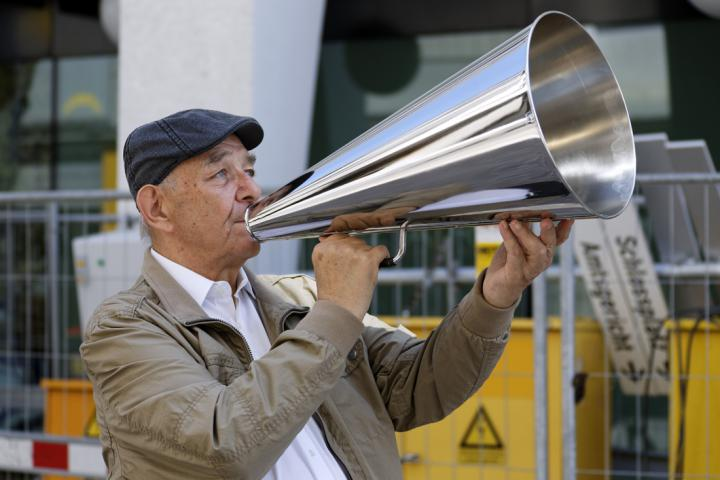 A man stands on the street with a silver megaphone