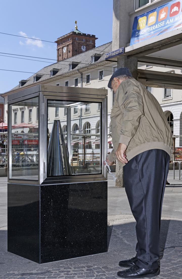 A man puts back a silver megaphone into a glass cabinet