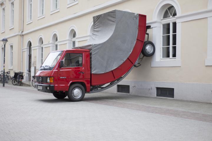 Ein roter Truck, dessen Hinterräder an der Wand stehen.