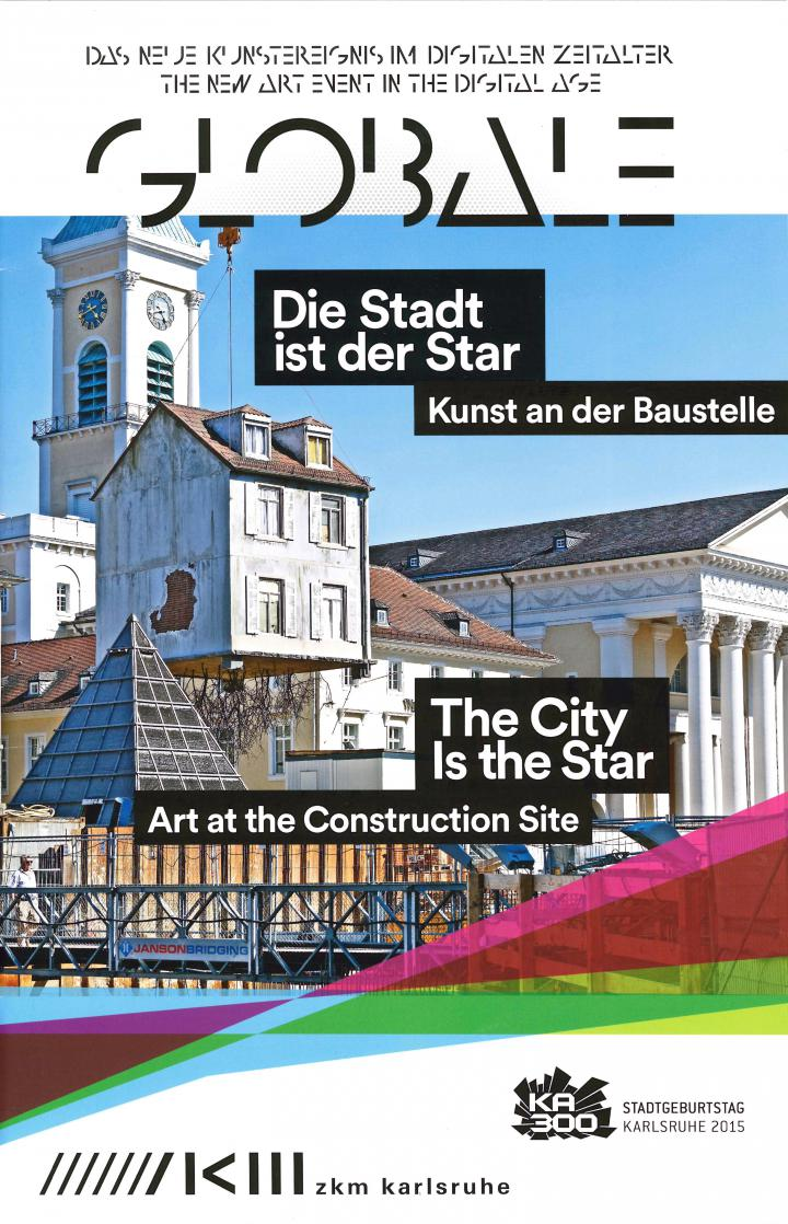 Blick auf den Marktplatz der Stadt Karlsruhe: An einem Kran hängt ein Haus, aus dessen Boden Wurzeln sprießen