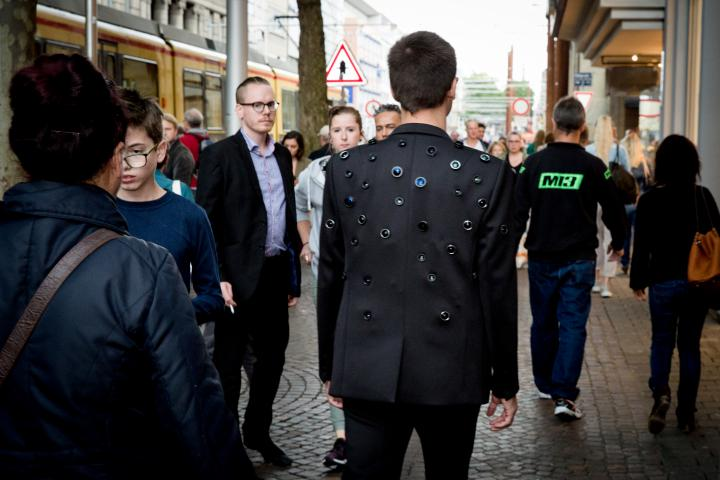 A Man wears a Jacket with some Camera-objectives in it