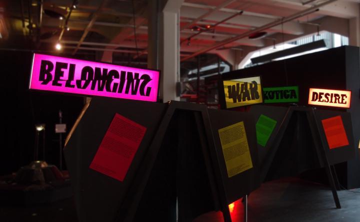 Blick in die Ausstellung: Leuchttafeln mit den Worten: Belonging, War, Desire.