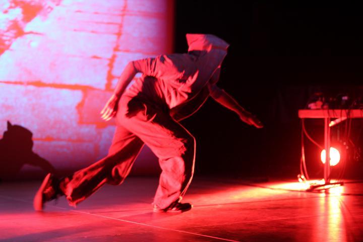 Ein Mann auf der Bühne mit Kapuzenjacke, in rotem Licht getaucht