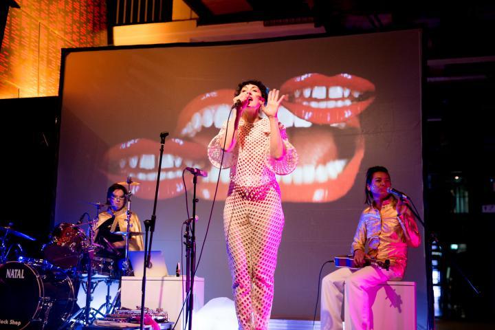 Drei Frauen auf der Bühne, auf der Leinwand im Hintergrund rote Münder