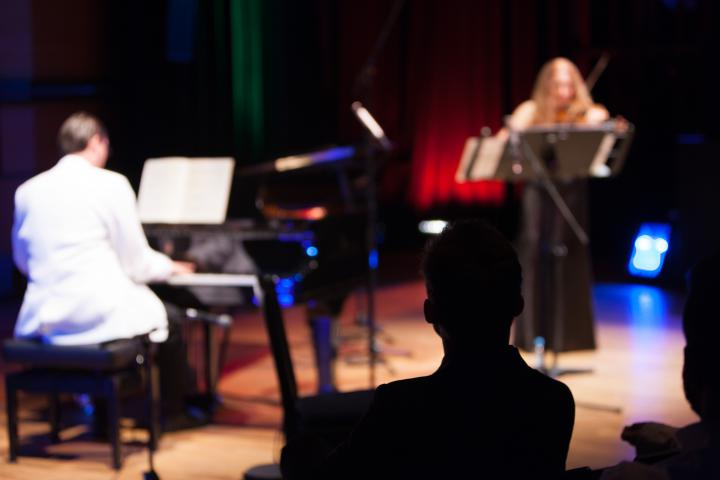 A man in a white suite playing piano. A woman in a black dress playing violin.