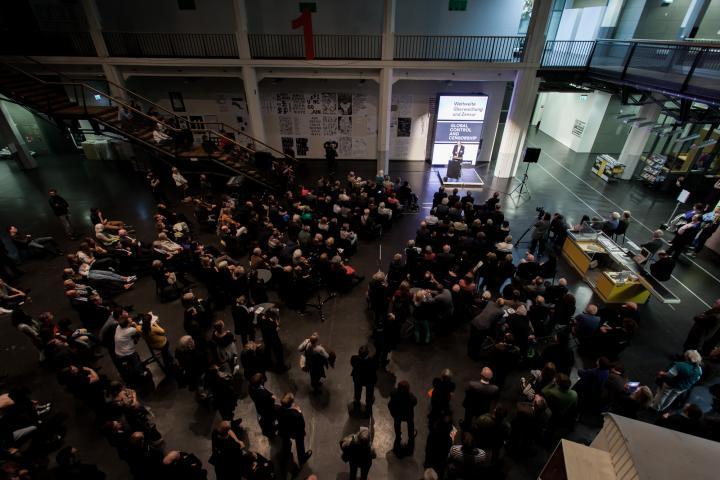 Blick von oben: Menschen stehen vor einer Bühne, auf der ein Mann eine Rede hält.