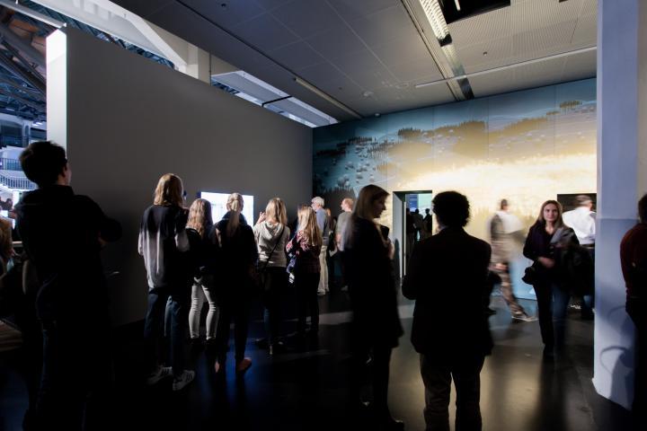 Viele Menschen stehen in einem Raum und schauen sich die Kunstwerke an