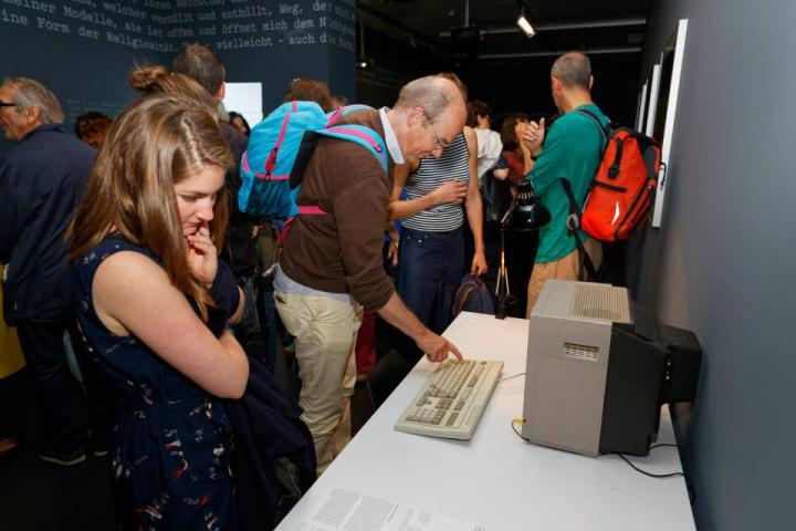 Menschen beugen sich vor einen alten Computer