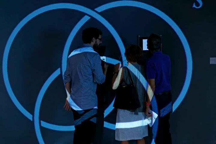 Drei Menschen stehen vor einer Wand. Auf sie werden blaue Kreise projiziert.