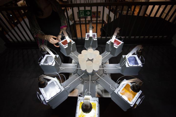 Eine Apparatur, in dessen Mitte 8 Flaschen verkehrt herum stecken. Dessen Inhalt wird an 8 Behältnisse übergeben