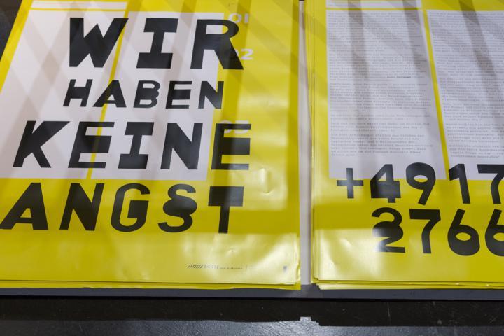 """Ein gelb-weißes Transparent auf dem steht: """"Wir haben keine Angst"""" und eine Telefonnummer"""