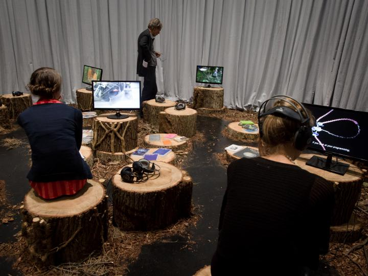 Persons sitting on tree trunks and watch videos