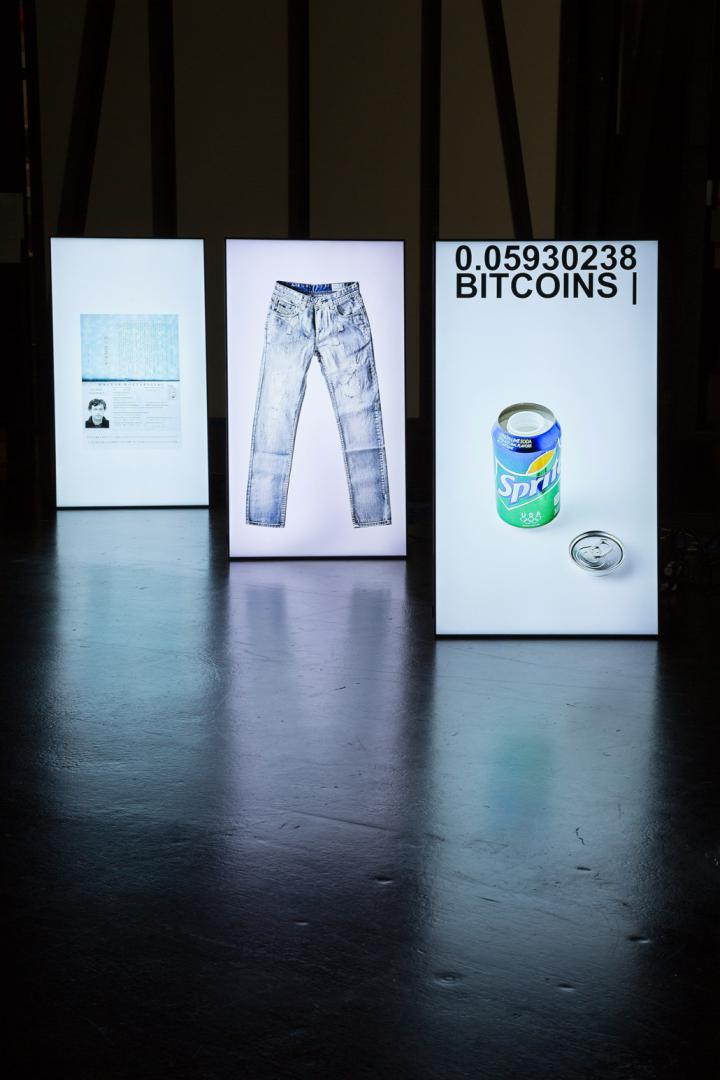 Three in a row standing luminous stands, on which a pair of pants, a sprite can and a card can be seen