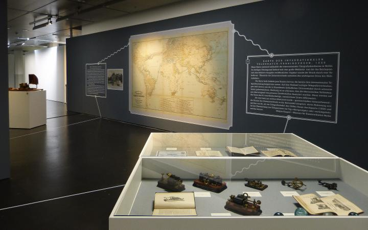 Schaukästen mit alten Telegrafen und eine große Landkarte an der Wand