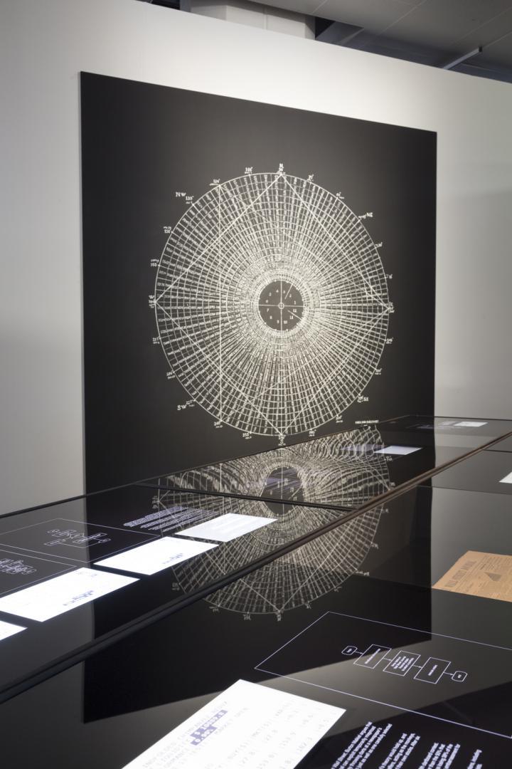 Ein Kreis voller Striche im Hintergrund. Im Vordergrund: Ein Vitrinentisch