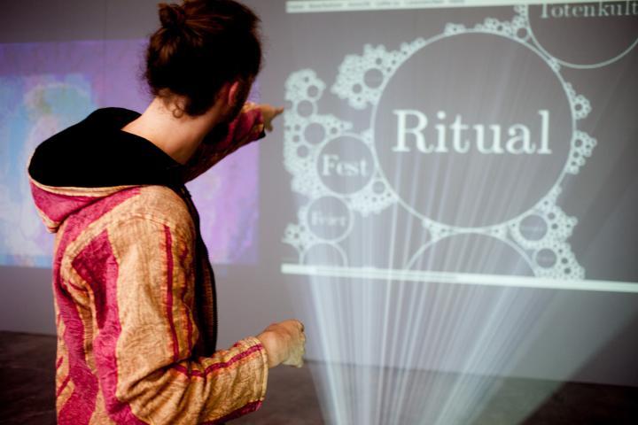 """Eine Person vor einer Projektion, auf der """"Ritual"""" steht"""