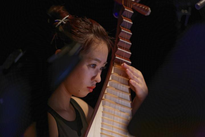 Eine Frau an einem Zupfinstrument