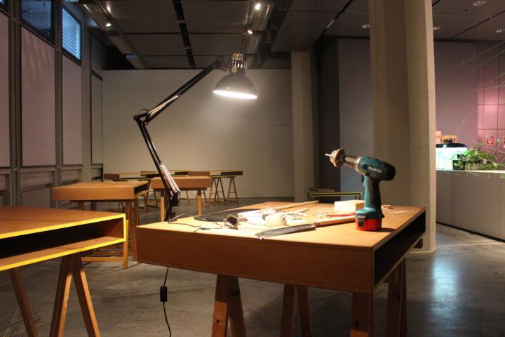 Ein Holztisch auf dem eine Lampe und eine Bohrmaschine steht