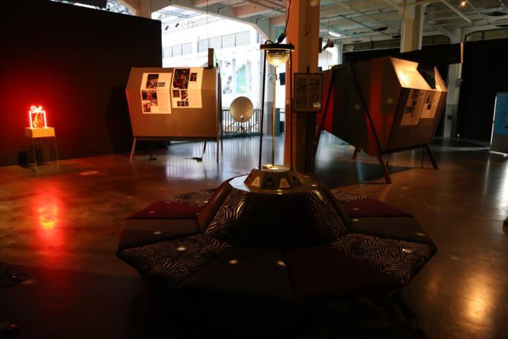 Ein in rötlichem Licht getauchter Raum, in dem verschiedene Tafeln stehen.