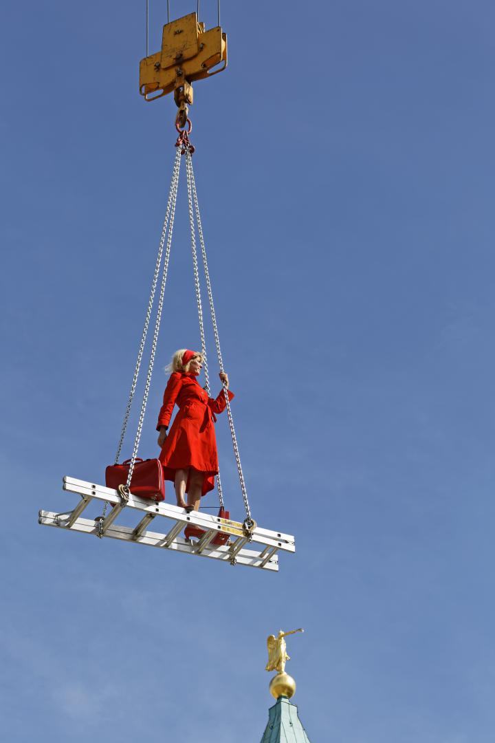 A blonde woman in a red dress on a floating ladder