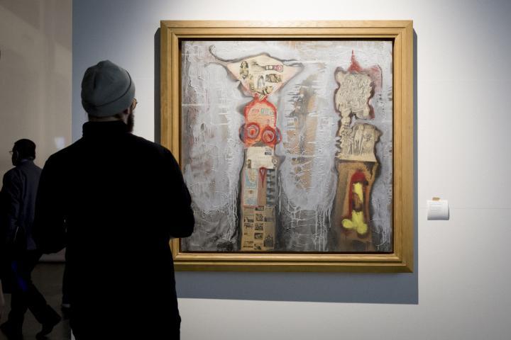 Ein Mann betrachtet ein abstraktes Gemälde