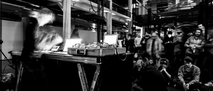 Mann steht hinter Mischpult zwischen Lautsprechersäulen