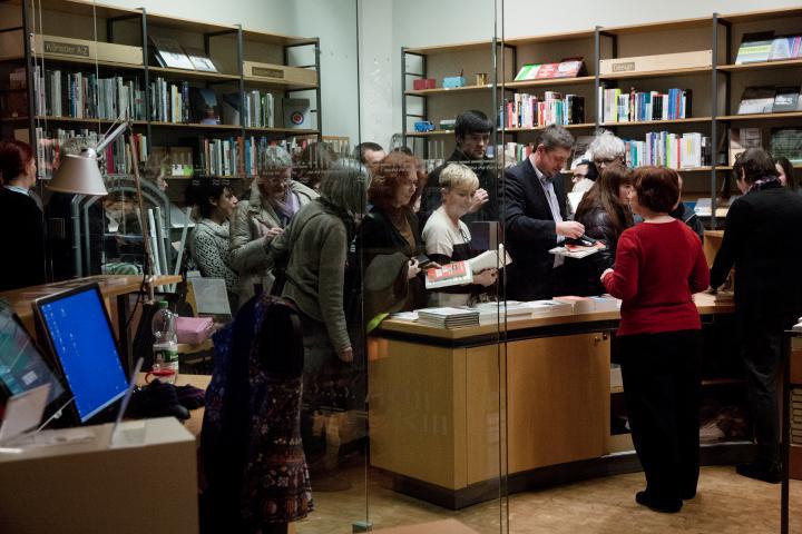 Menschen stehen vor einem Tresen voller Bücher