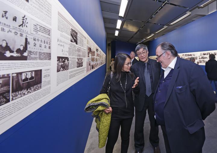 Drei Menschen sprechen vor einigen ausgestellten Bildern miteinander