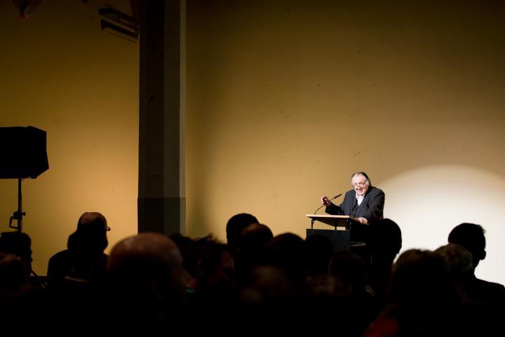 Ein Mann steht vor einem Pult und spricht zum Publikum
