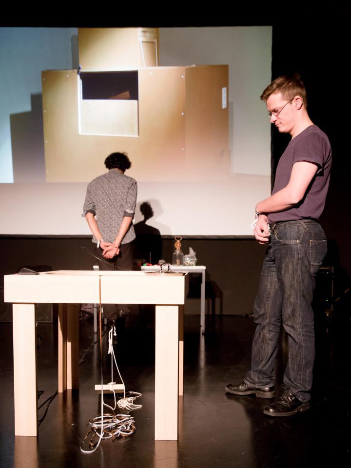Zwei Männer. Einer steht mit dem Rücken zum Publikum. Der andere steht seitlich und schaut auf einen Tisch