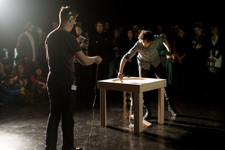Zwei Männer. Einer hält einen Bindfaden, der an einem Tisch befestigt ist. Der andere kreist mit einem Stöckel in einem in ein Tisch gefrästen Kreis