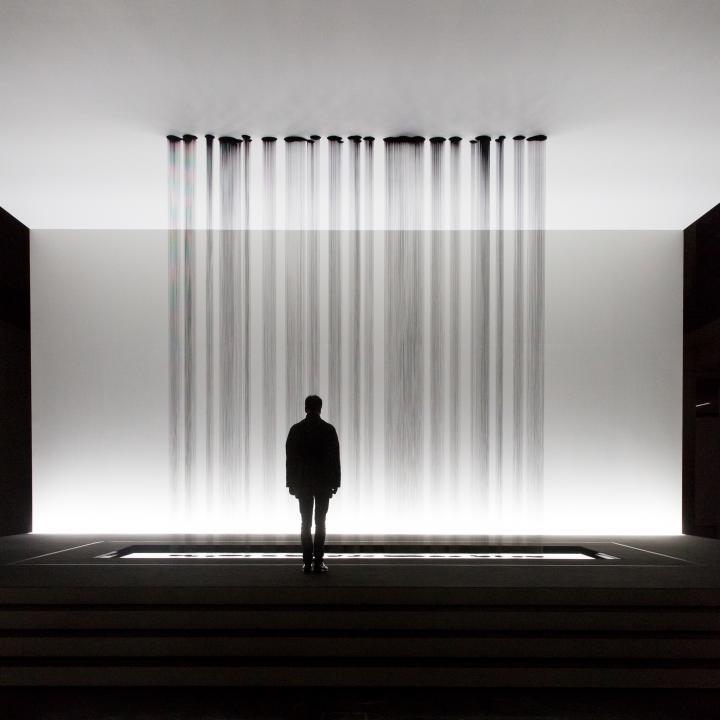 Eine Person steht vor einer Skulptur, bei der mehrere Rinnsale von Öl auf den Boden tropfen