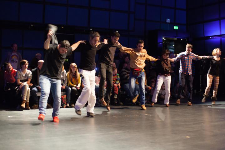 Young men standing in a row and dance