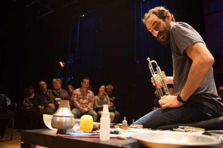 A man sits on the ground and presents different instruments