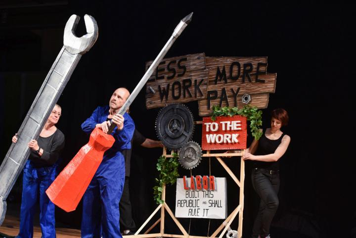 Three people fiddling with oversized tools made of paper mache
