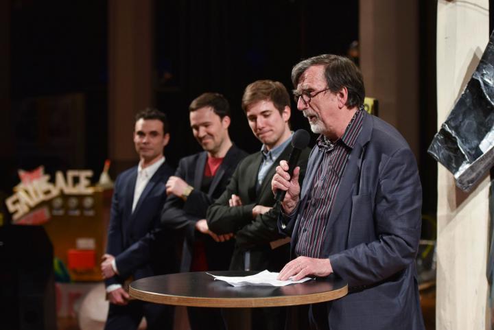 Ein Mann spricht zum Publikum. Hinter ihm stehen drei weitere Männer