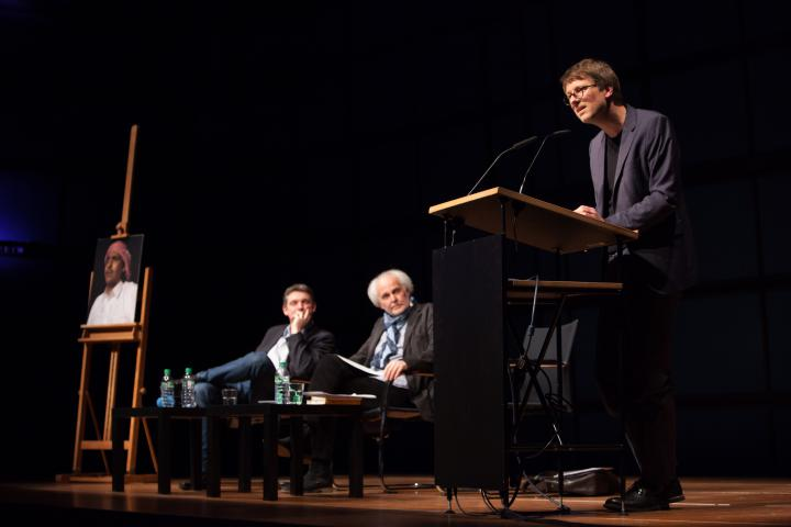 Links: An easel with a picture of a man with a turban. Middle: Two men sitting on chairs. Right: A man standing at a podium and addresses the audience.