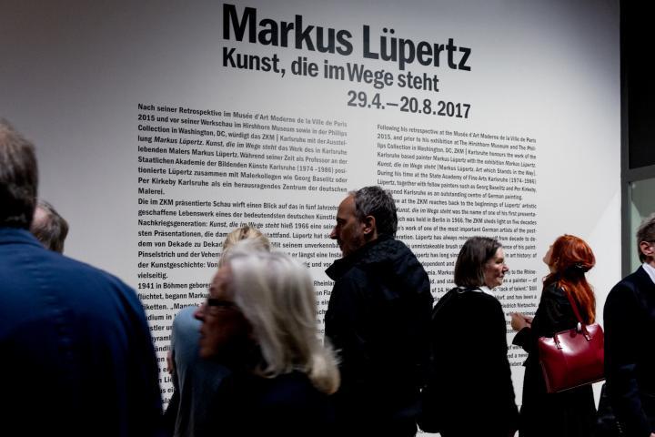 Das Bild zeigt Besucher vor einer Informationstafel zu Markus Lüpertz