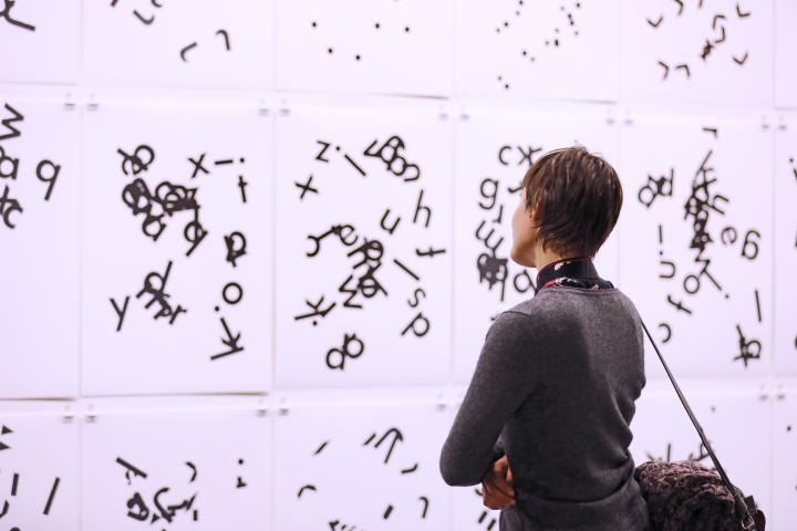Besucherin am Eröffnungsabend vor einer Collage von Hansjörg Mayer