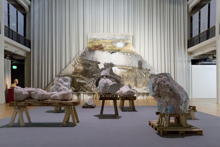 Eine zerstückelte Beton-Skulptur auf Böcken vor einer Vorzeichnung