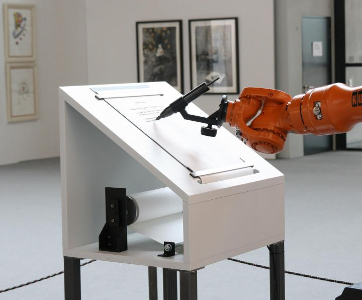 The picture shows a robot arm writing a manifesto