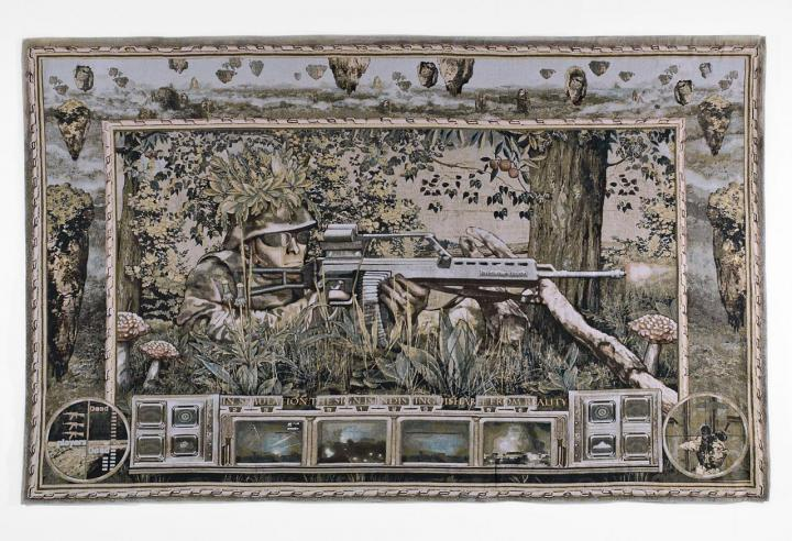 Gewebte Darstellung eines liegenden Soldaten mit Gewehr in einer Waldlandschaft