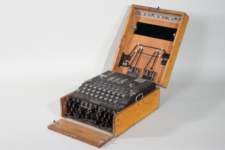Schwarze Apparatur mit Tasten und Kabeln in einer Holzkiste